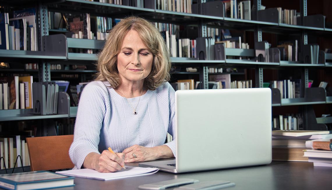 item 13 of Gallery image - Mujer en una biblioteca tomando notas y con una computadora sobre la mesa