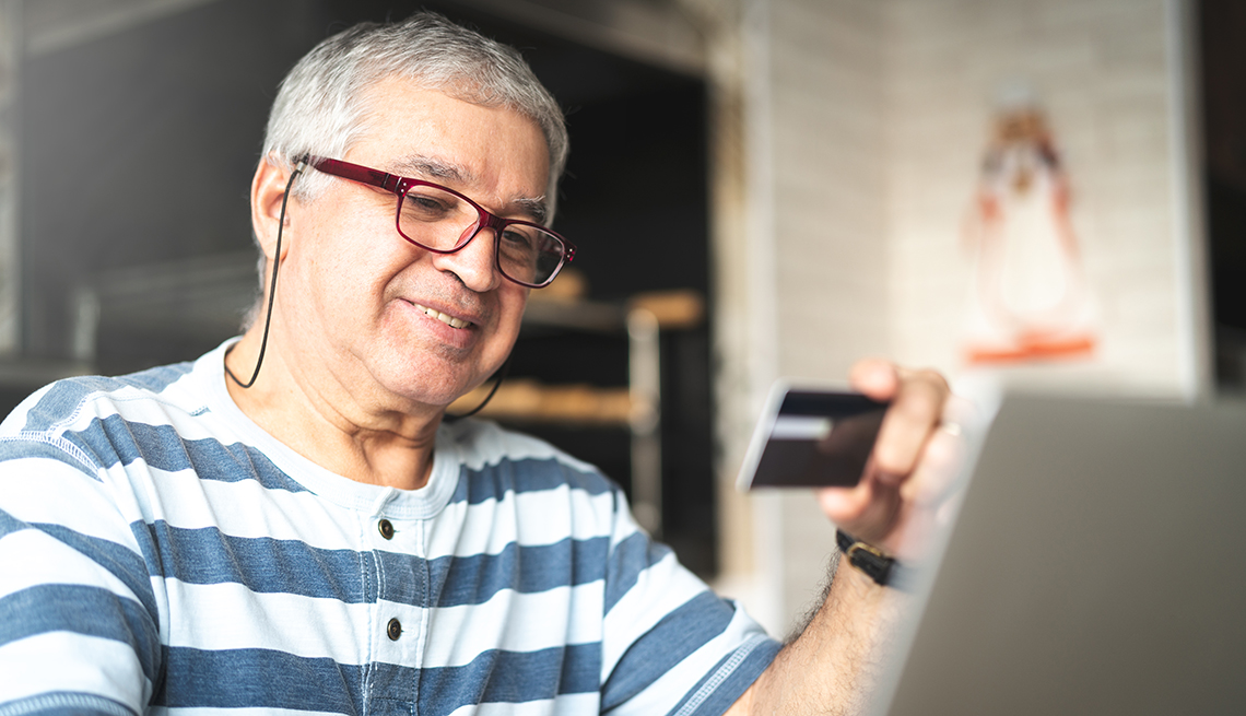 item 4 of Gallery image - Hombre con una tarjeta en la mano y viendo una computadora