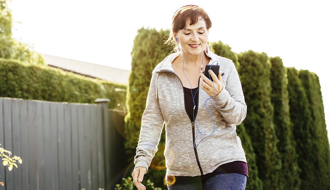 item 16 of Gallery image - Mujer caminando mientras mira su teléfono móvil