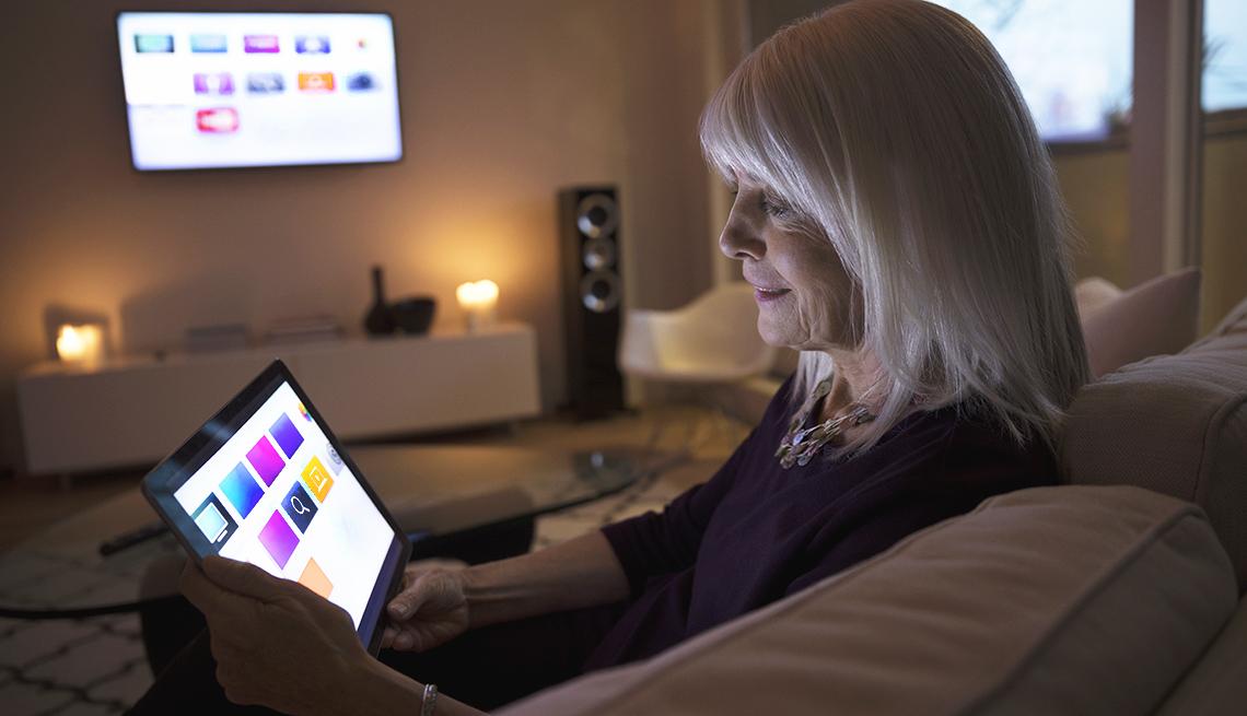item 5 of Gallery image - Mujer mirando una tableta sentada en la sala de una casa