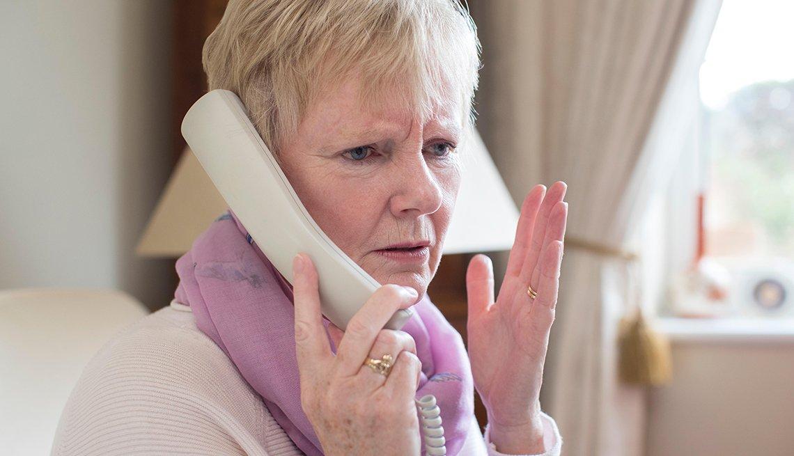 Mujer hablando por un teléfono fijo
