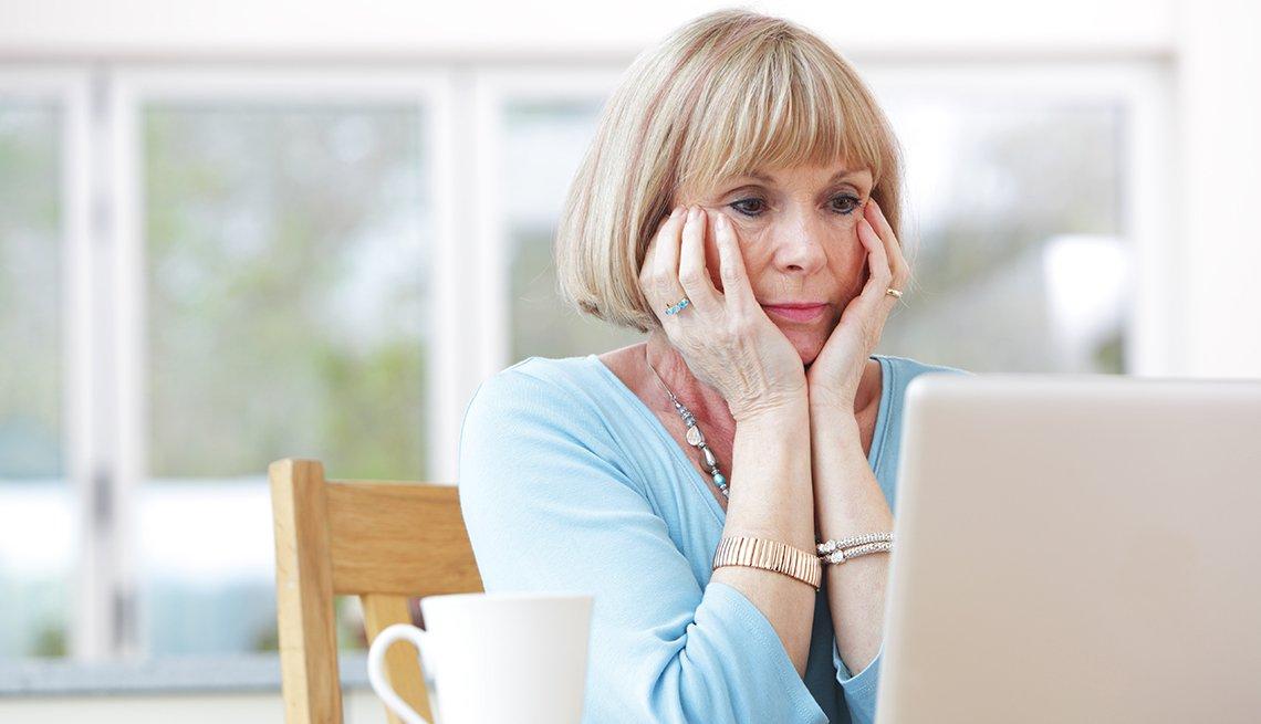 Mujer con las manos en la cara y viendo una computadora portátil