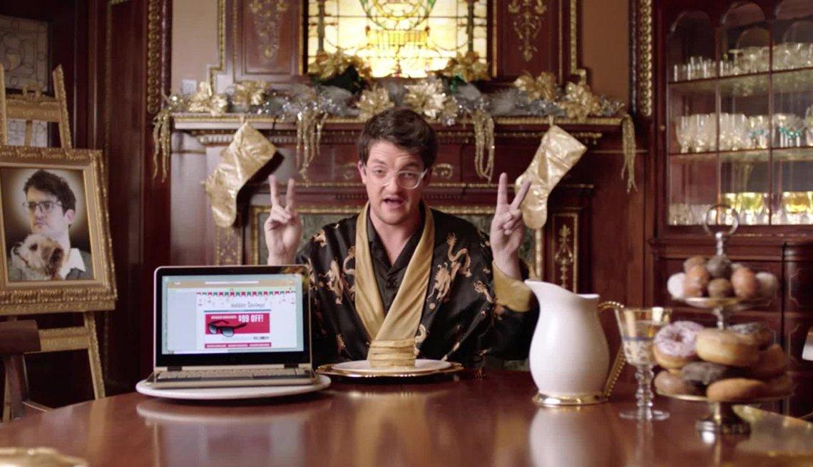 Hombre en una bata de levantar sentado en un comedor y con una computadora al lado