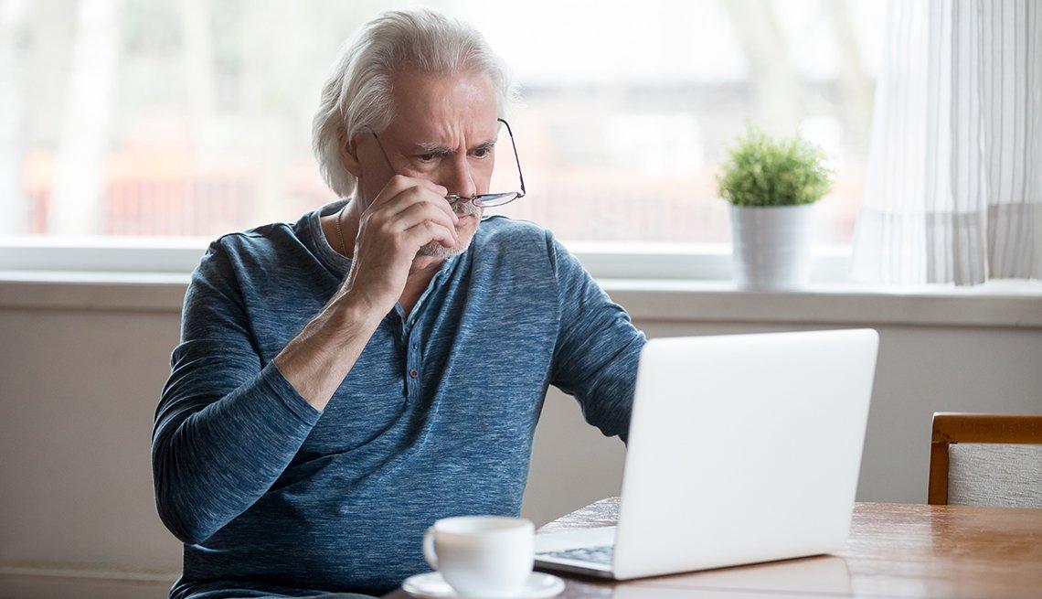Hombre mirando a la pantalla de una computadora portátil.