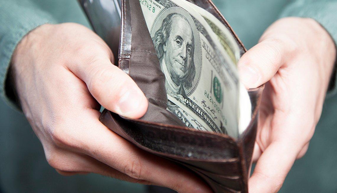 Hombre sosteniendo una billetera con dólares.