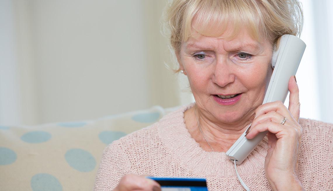 Mujer mayor hablando por teléfono y mirando una tarjeta de crédito.