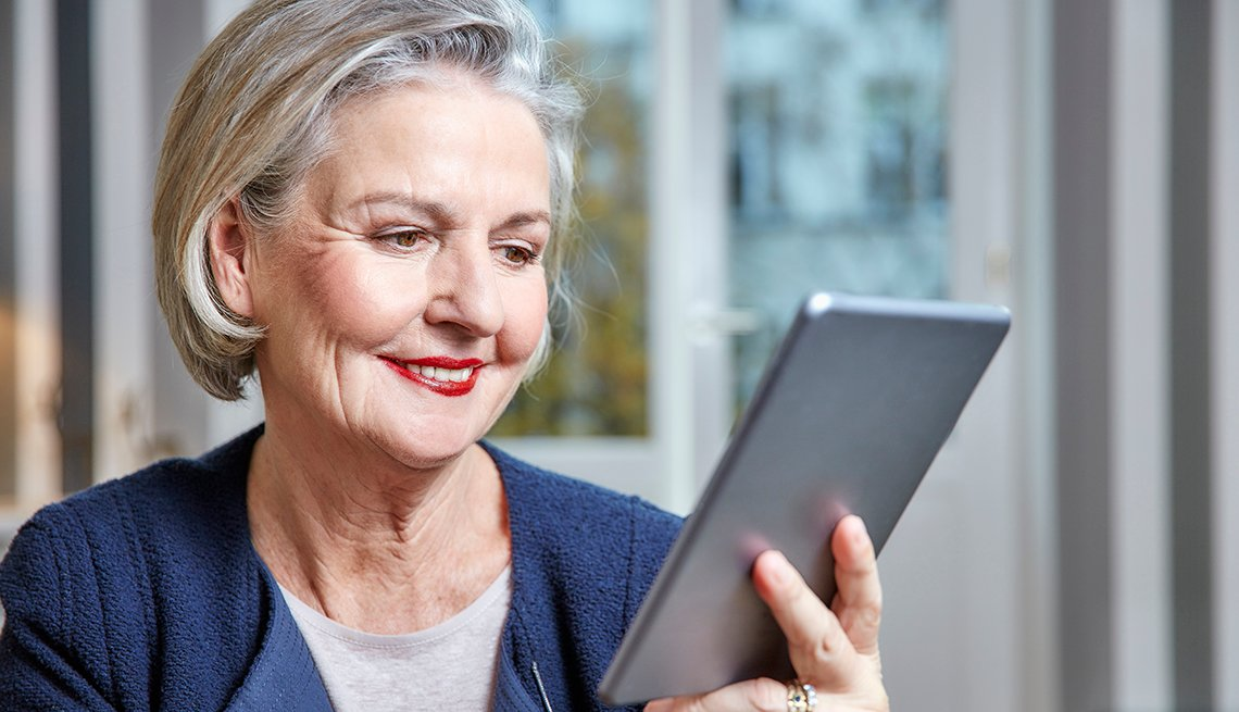Mature woman smiling at her tablet