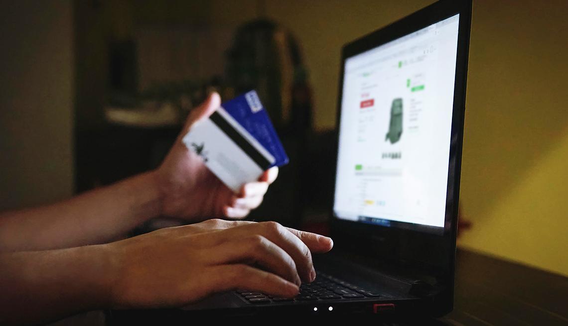 Persona usa una tarjeta de crédito para comprar por internet