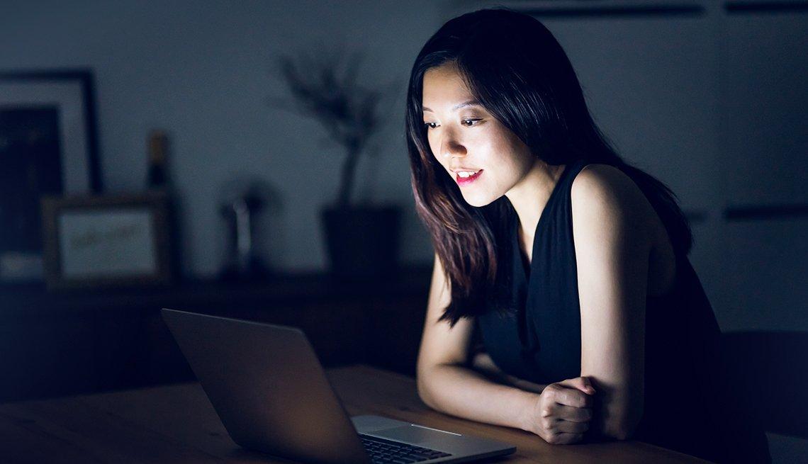 Mujer asiática mirando a su computadora.