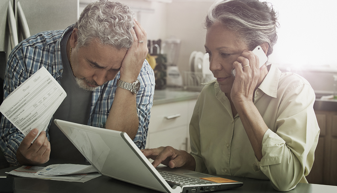 Stressed mature couple reviewing financial statements for suspicious activity