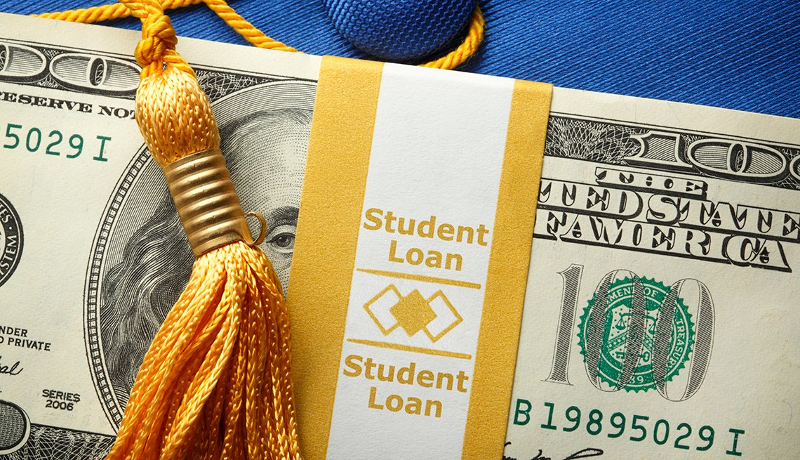 """A stack of one hundred dollar bills in a money wrapper labeled """"Student Loan"""" on top of a blue graduation cap.  A gold graduation tassel is draped over the stack of money."""