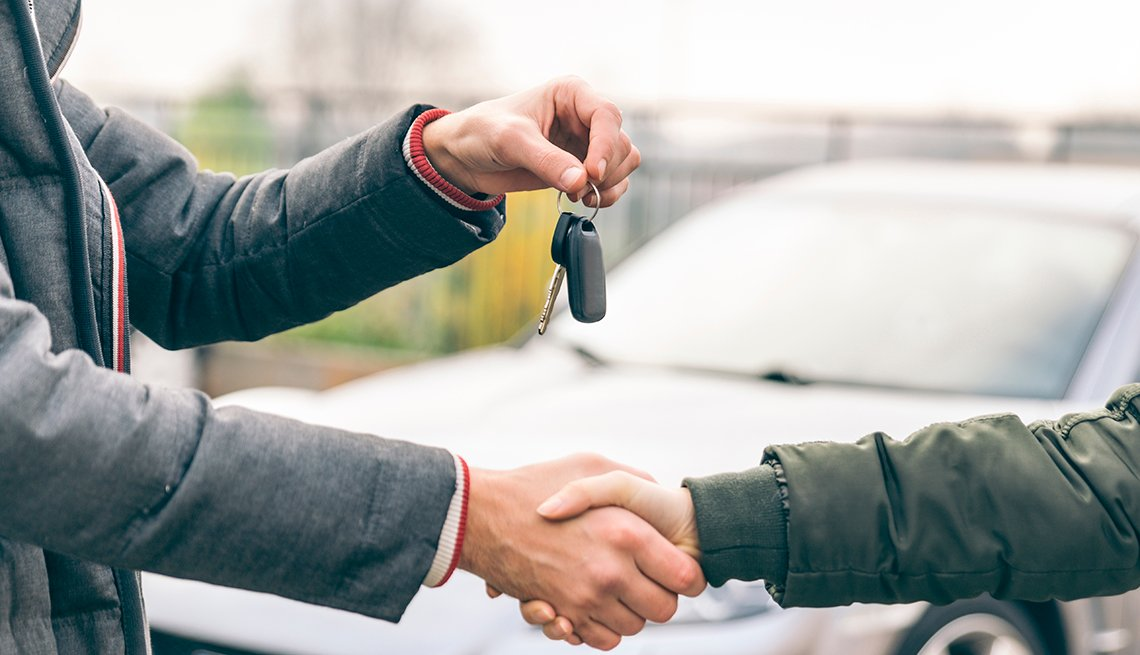 Two people shaking hands as one person hands over car keys, with a car pictured in the background