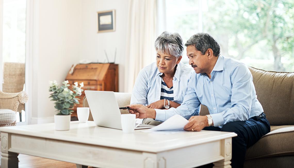 Pareja mayor sentada en la sala de su casa y revisando cuentas en una computadora portátil.
