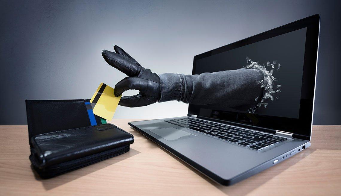 Mano saliendo del computador y sacando una tarjeta de crédito de una billetera
