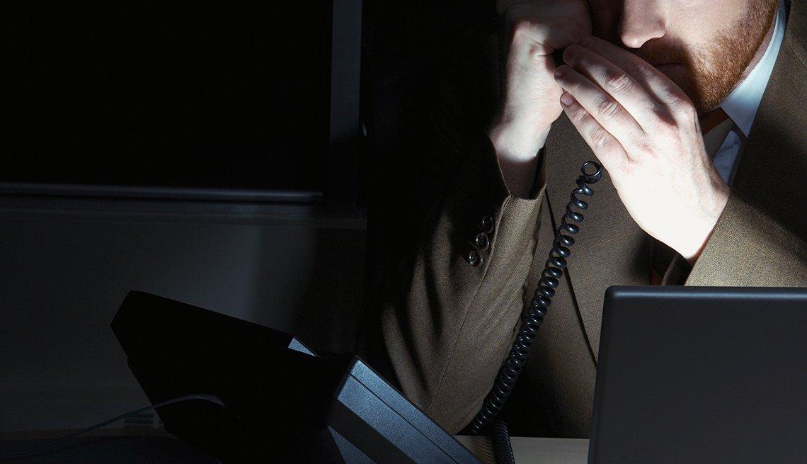 man talking on phone in dark room