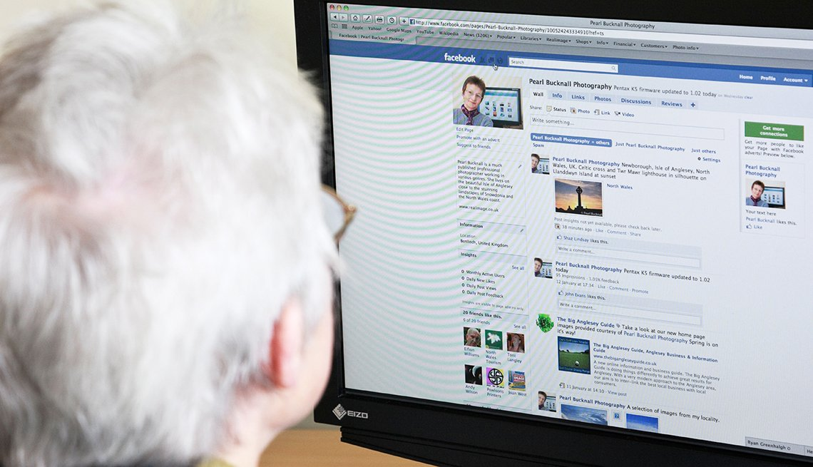 Senior woman using Internet to look at this photographers business page on Facebook social media website webpage on a home computer.