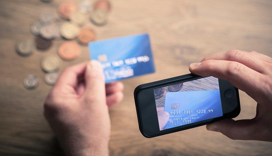 Un hombre usa su teléfono para fotografiar una tarjeta de crédito