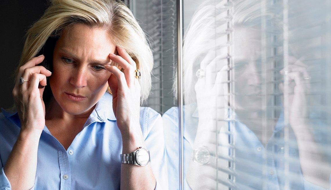 Mujer apoyándose en una ventana y con cara de preocupación