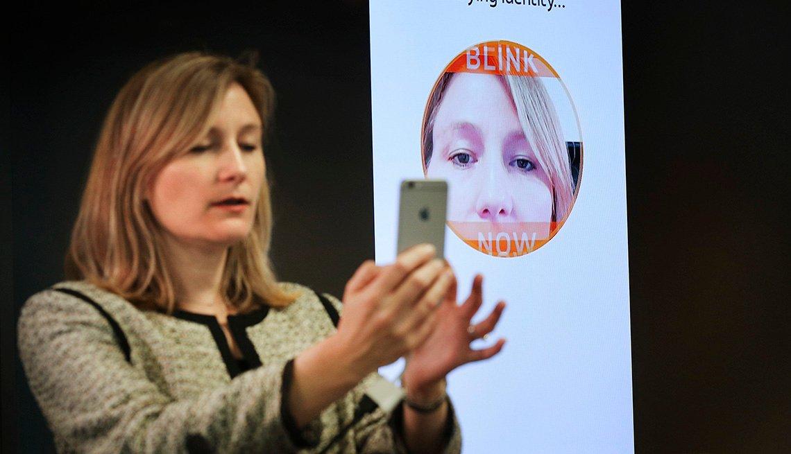 Mujer sostiene un teléfono inteligente para demostrar la tecnología de reconocimiento facial