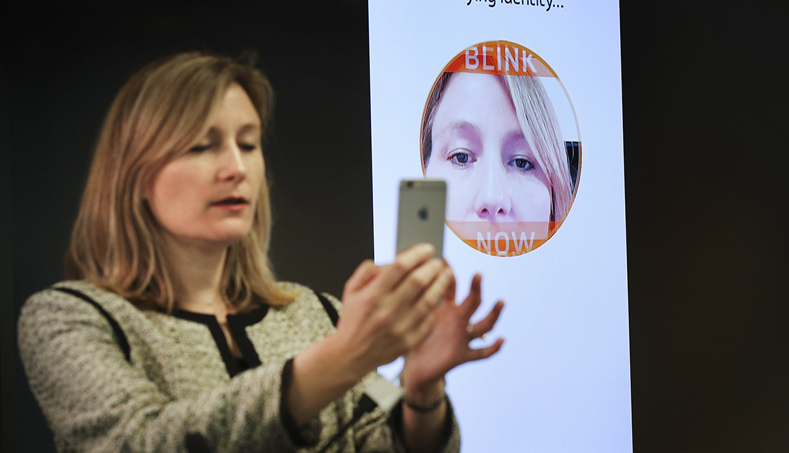 Woman holds a smartphone to her face, demonstrating facial recognition technology