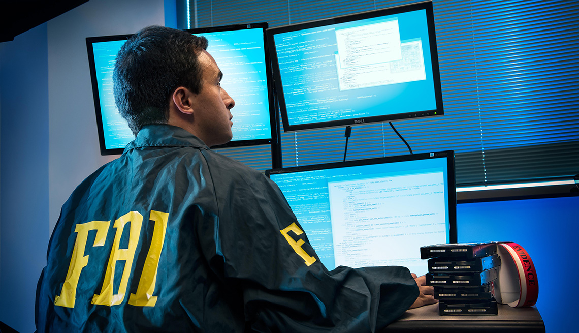 A man with a FBI logo jacket sits in front of computer screens
