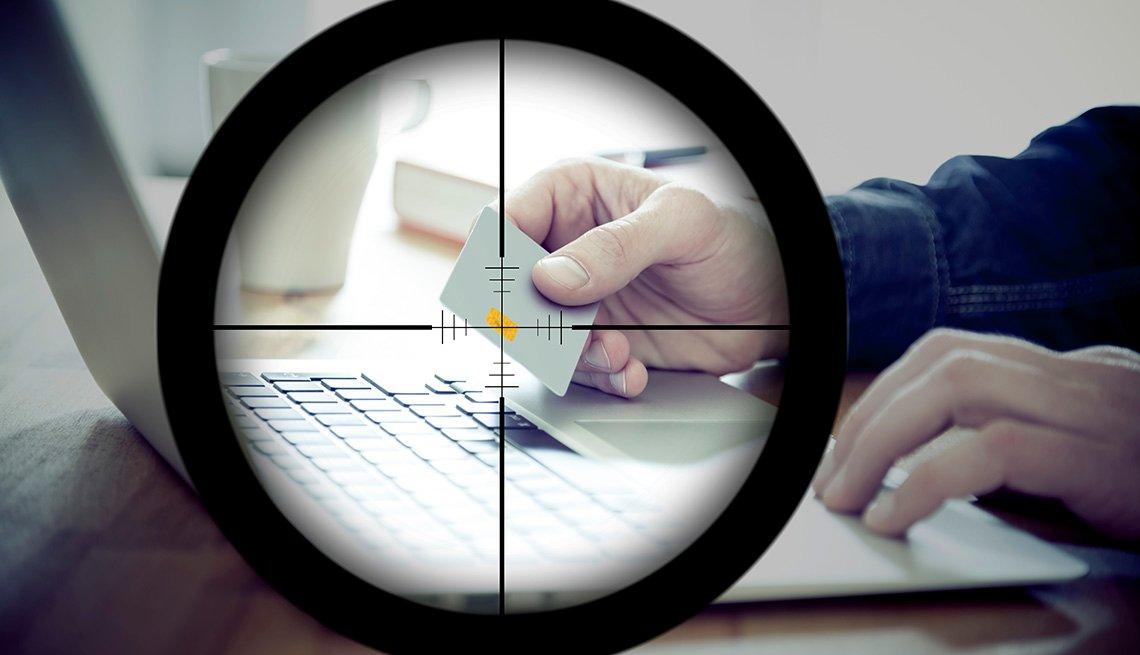 En una mira telescópica se puede observar una persona usando una tarjeta de crédito en frente del computador
