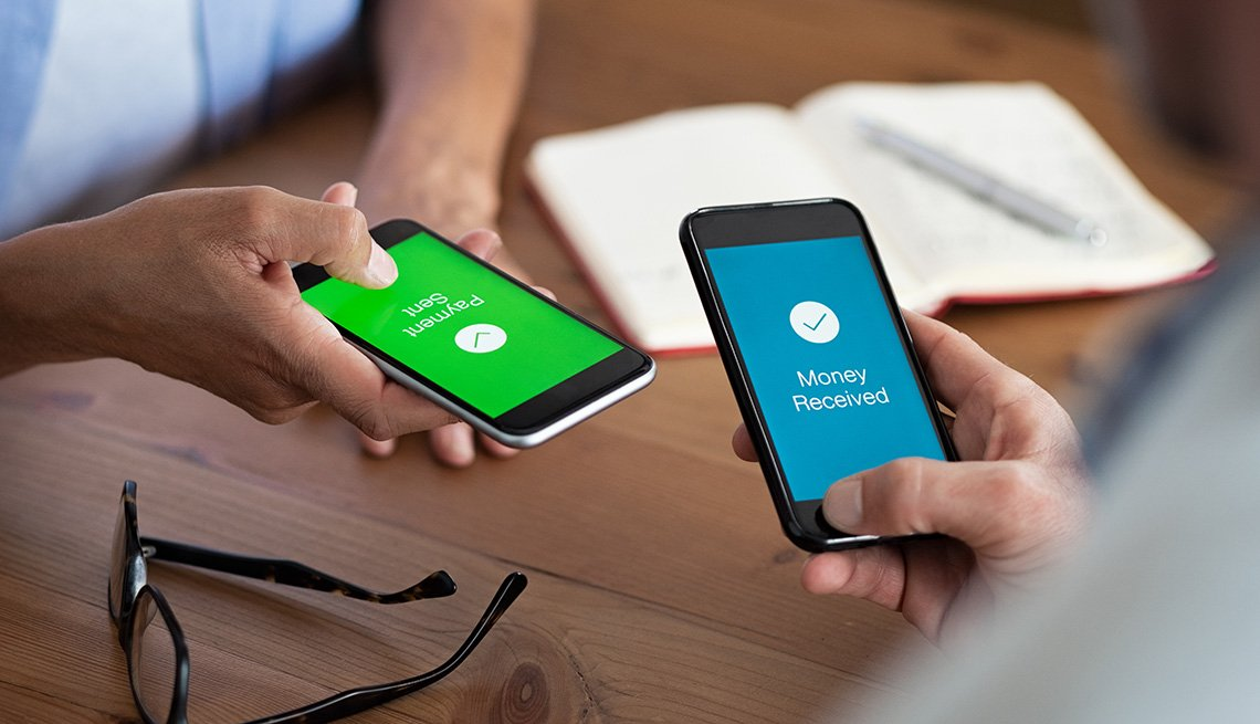 Un hombre y una mujer sostienen sus teléfonos inteligentes mientras hacen una transacción de pago electrónico