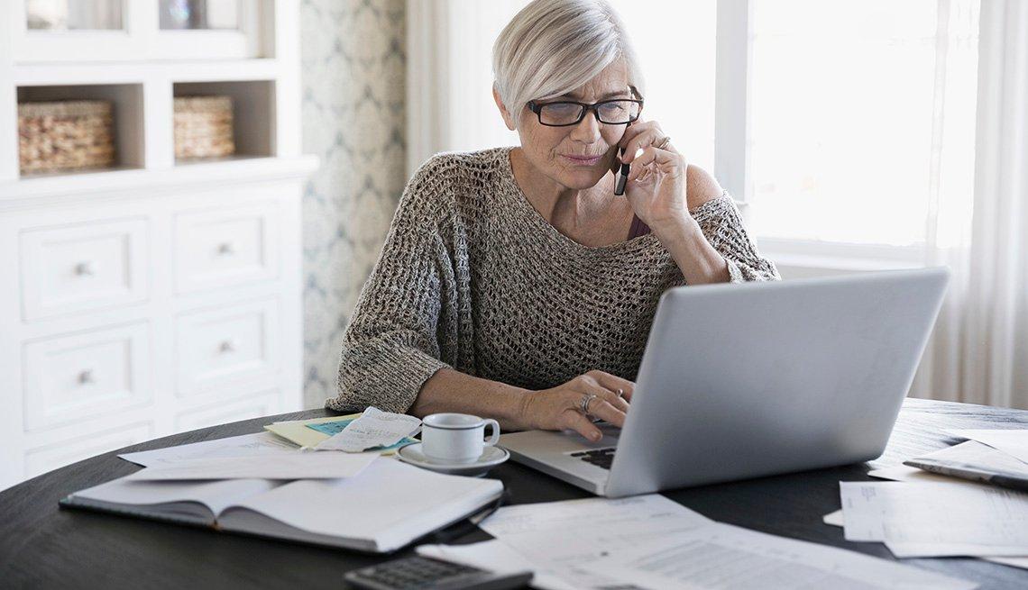 Mujer sostiene teléfono inteligente en su oído y mira a una computadora portátil