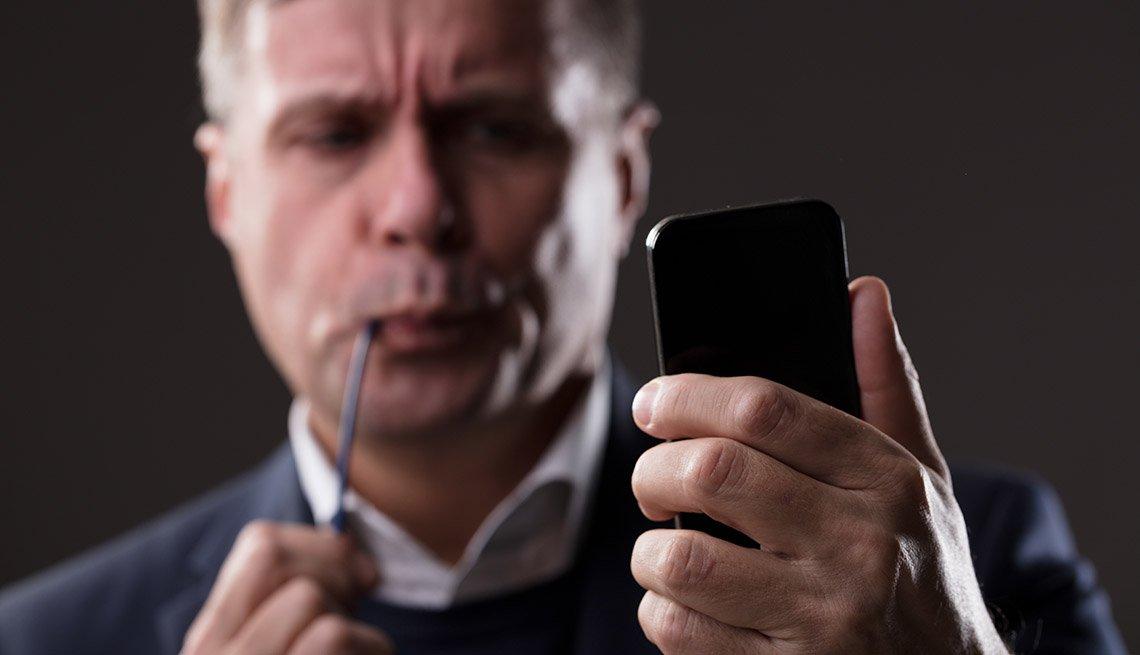 Hombre fumando una pipa y con un teléfono móvil en la mano.