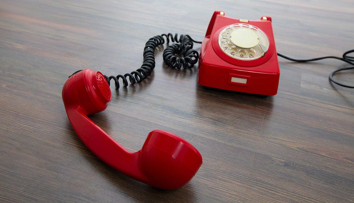 Teléfono rojo y antiguo en el piso