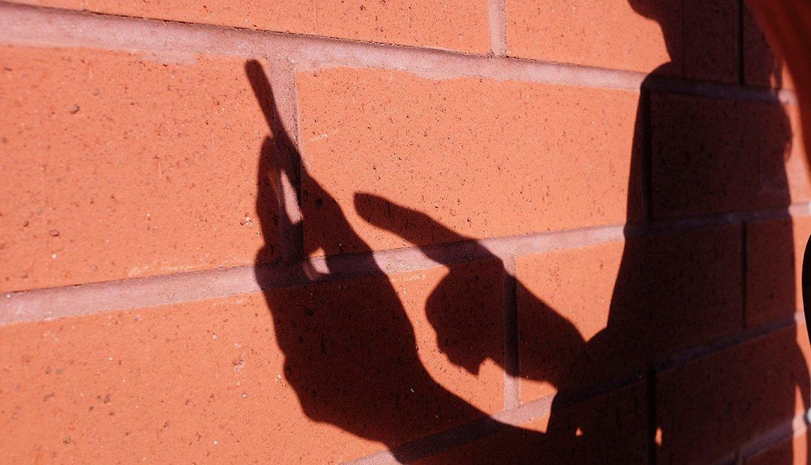 Sombra de una mujer usando un teléfono inteligente sobre un muro de ladrillo