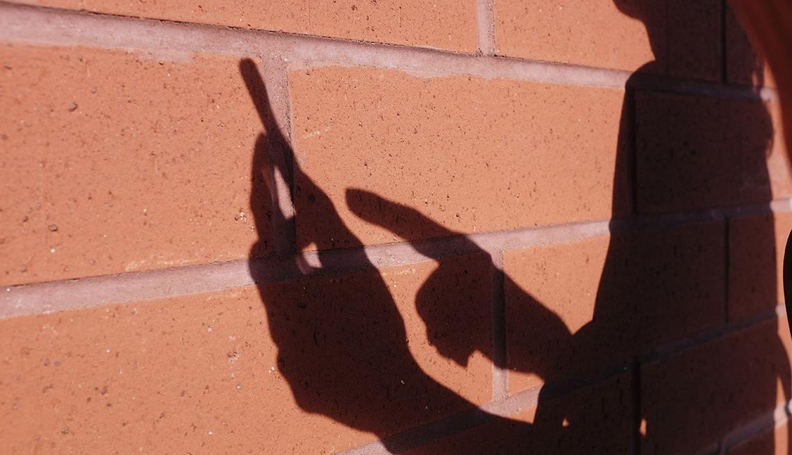 Woman's shadow on brick wall, using smart phone