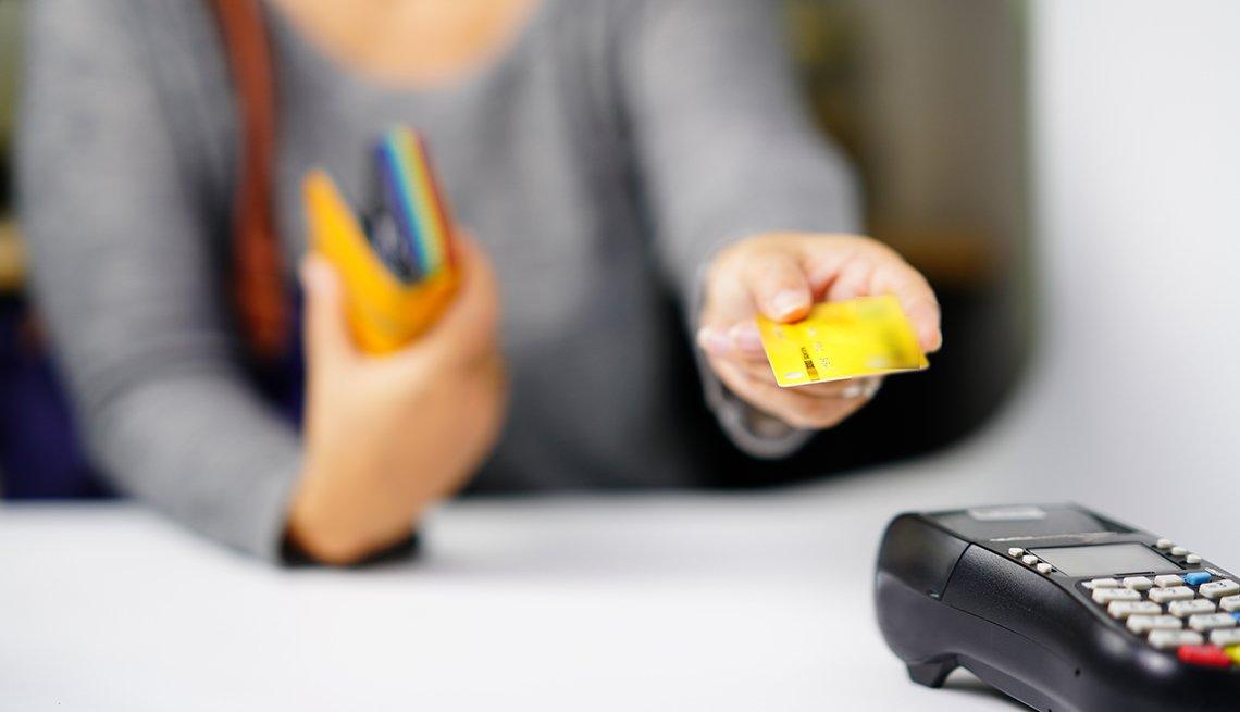 Mujer con una tarjeta de regalo frente a un datáfono.