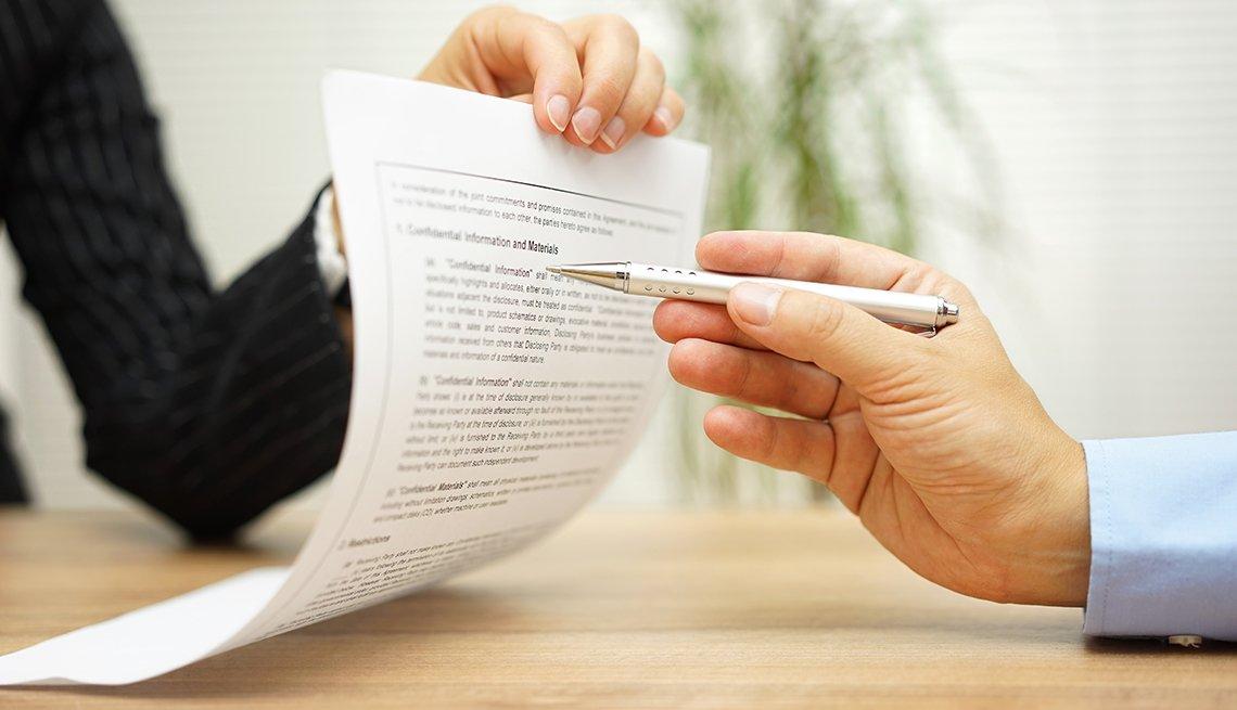 Una mano sostiene un contrato y otra lo revisa.