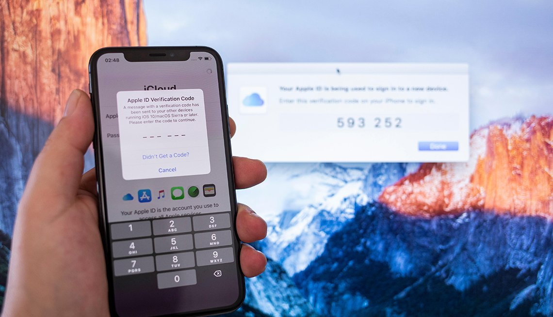 Mano sosteniendo un teléfono inteligente de Apple que verifica la cuenta con un código.