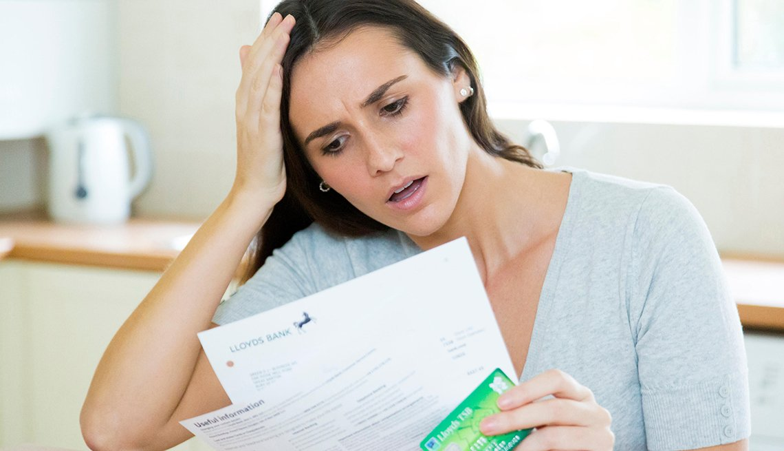 Worried woman reviews her bank statement, afraid that there may be fraudulent charges.