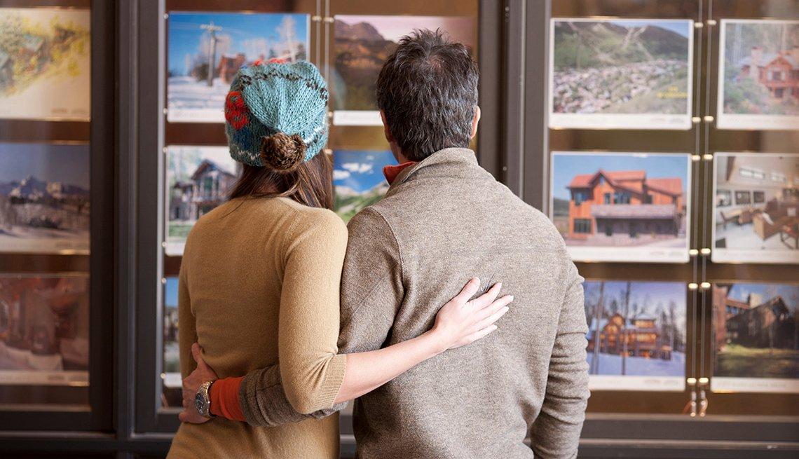 Pareja viendo opciones de viaje en fotos colgadas en un muro de una oficina de viajes.
