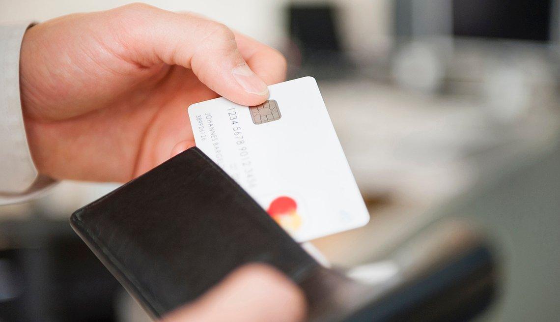 Manos sacando una tarjeta de crédito de una billetera.