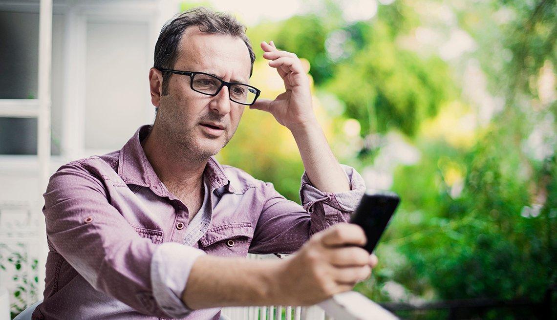Hombre mirando un teléfono celular sentado en un balcón.