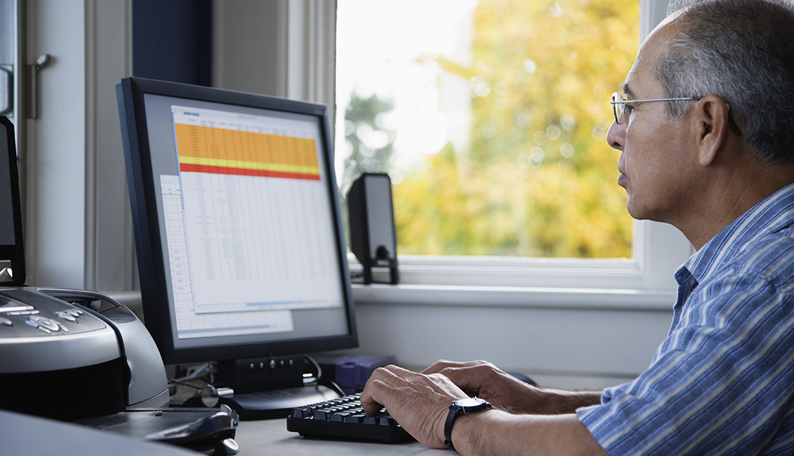 Hombre sentado mirando la pantalla de su computadora
