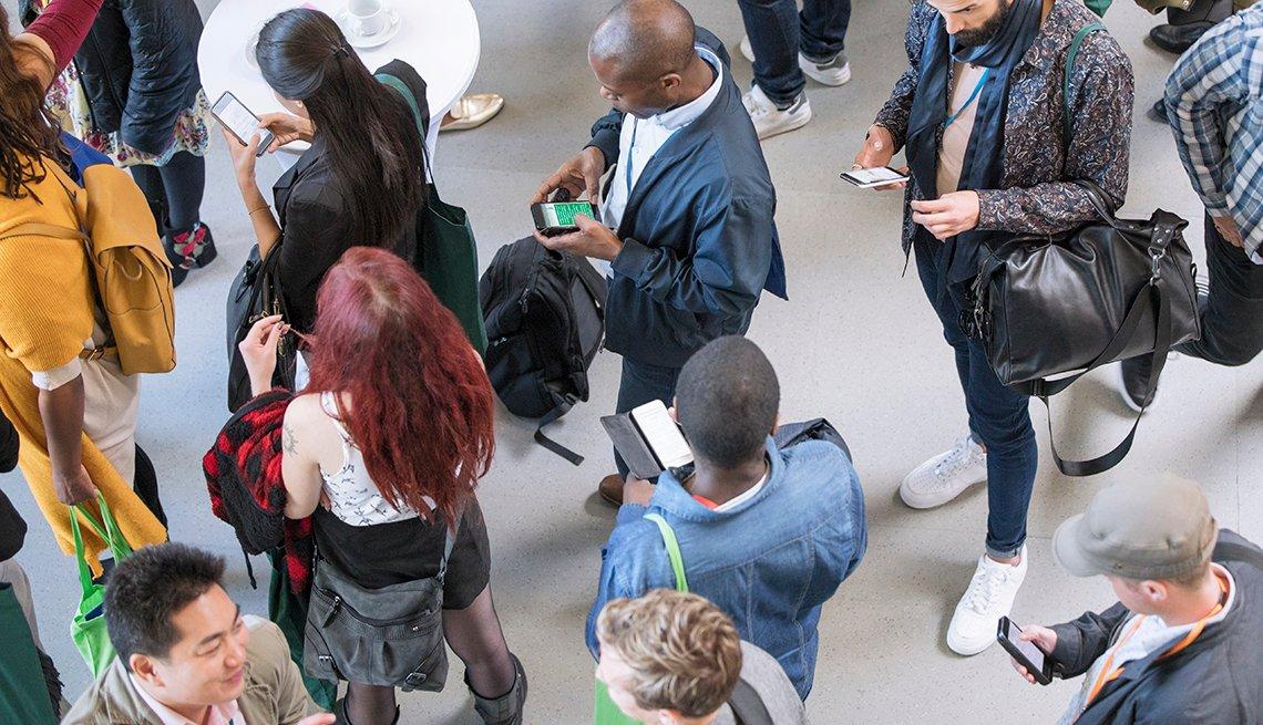 Personas mirando sus teléfonos y en una fila.