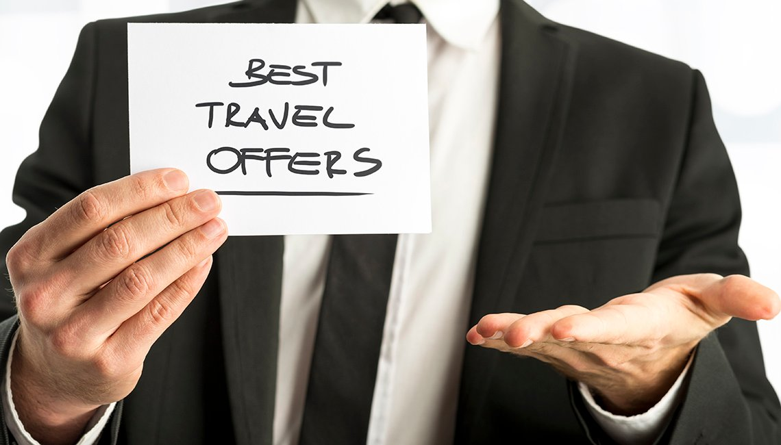 "Man holding paper saying ""Best travel offers"""