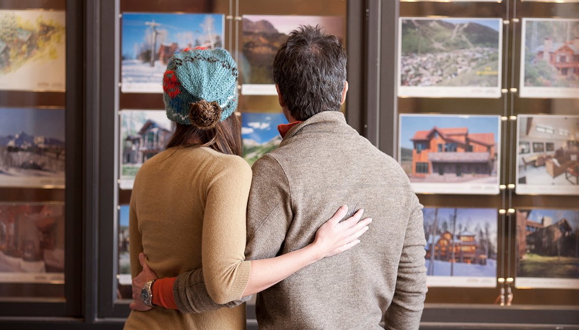 Couple looking through holiday vacation packages at travel agents office