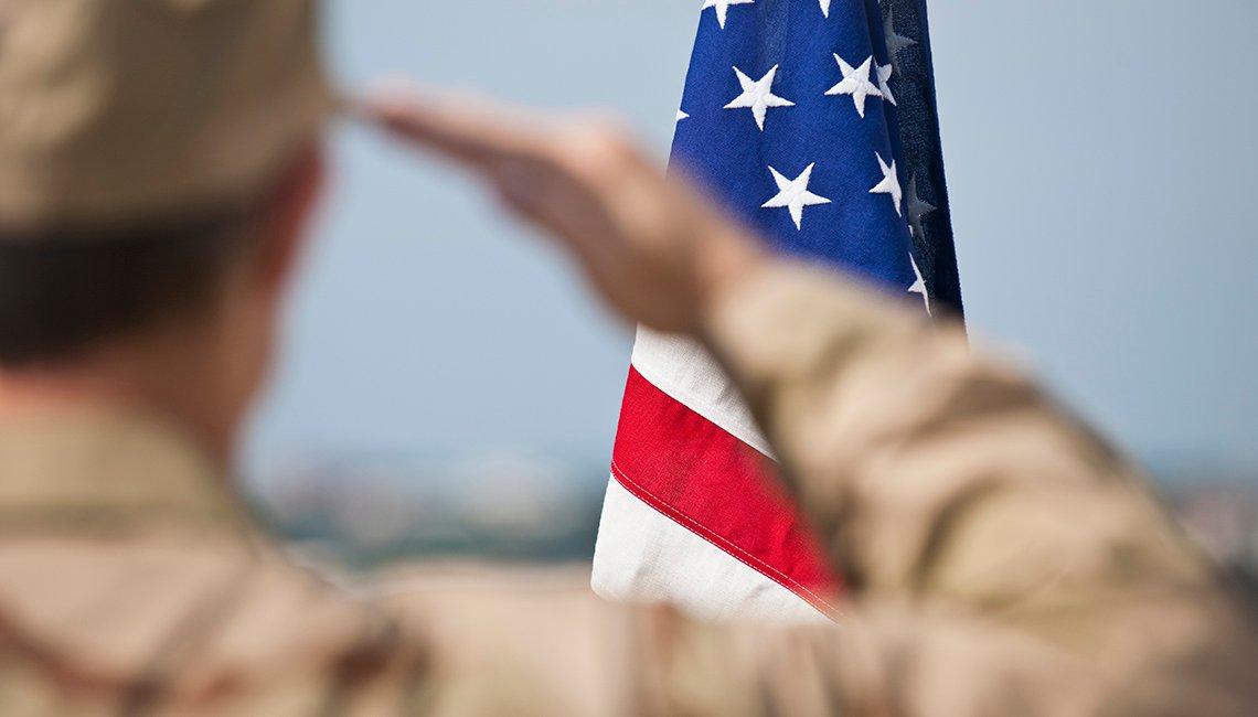 Militar saludando la bandera de Estados Unidos.