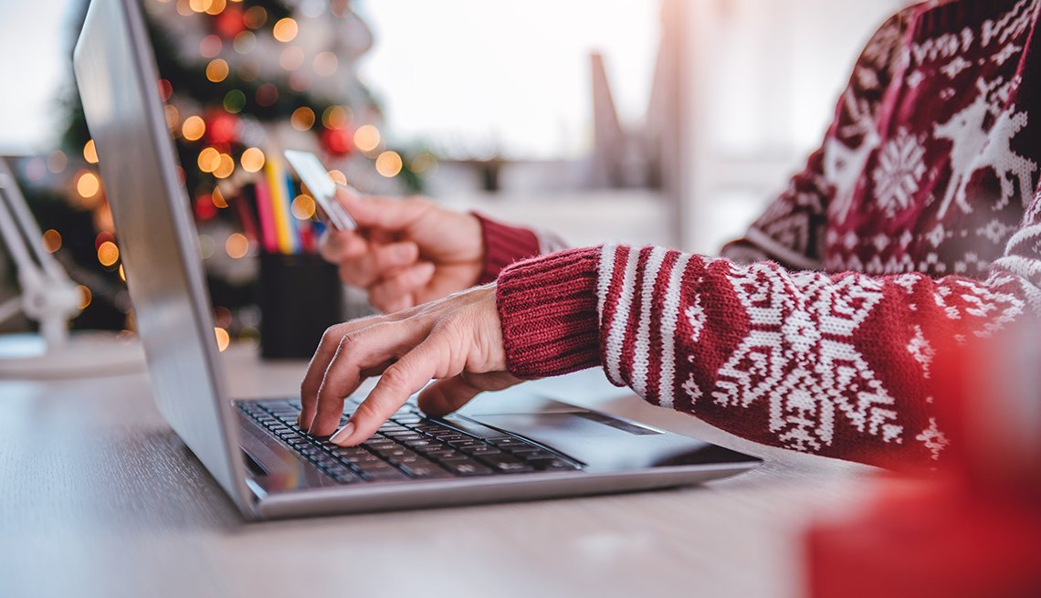 A person wearing a red sweater shopping online during the holidays