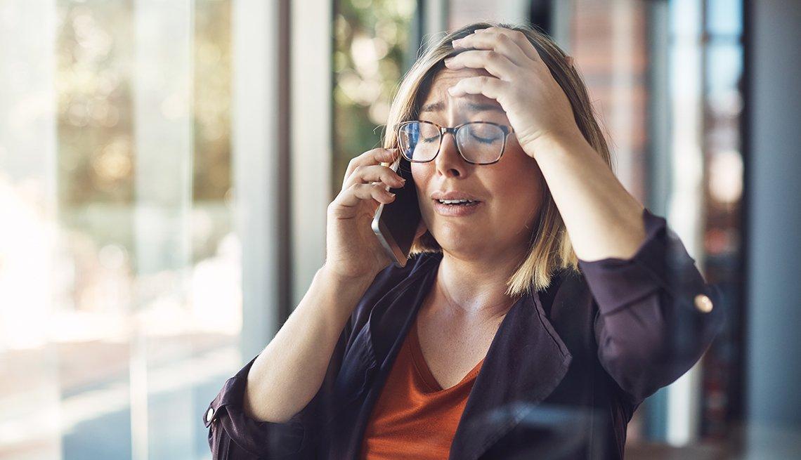 Mujer con expresión de preocupación con una mano en la cabeza y la otra sostiene el teléfono.