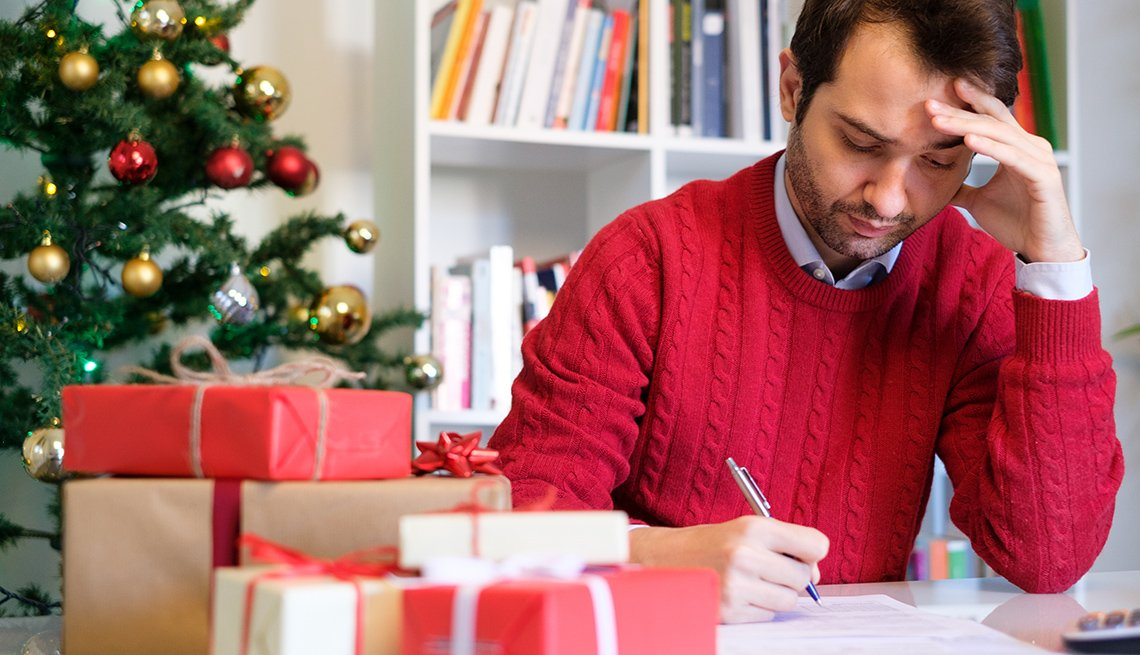 Hombre haciendo cuentas en su escritorio con regalos y un árbol de navidad al fondo.