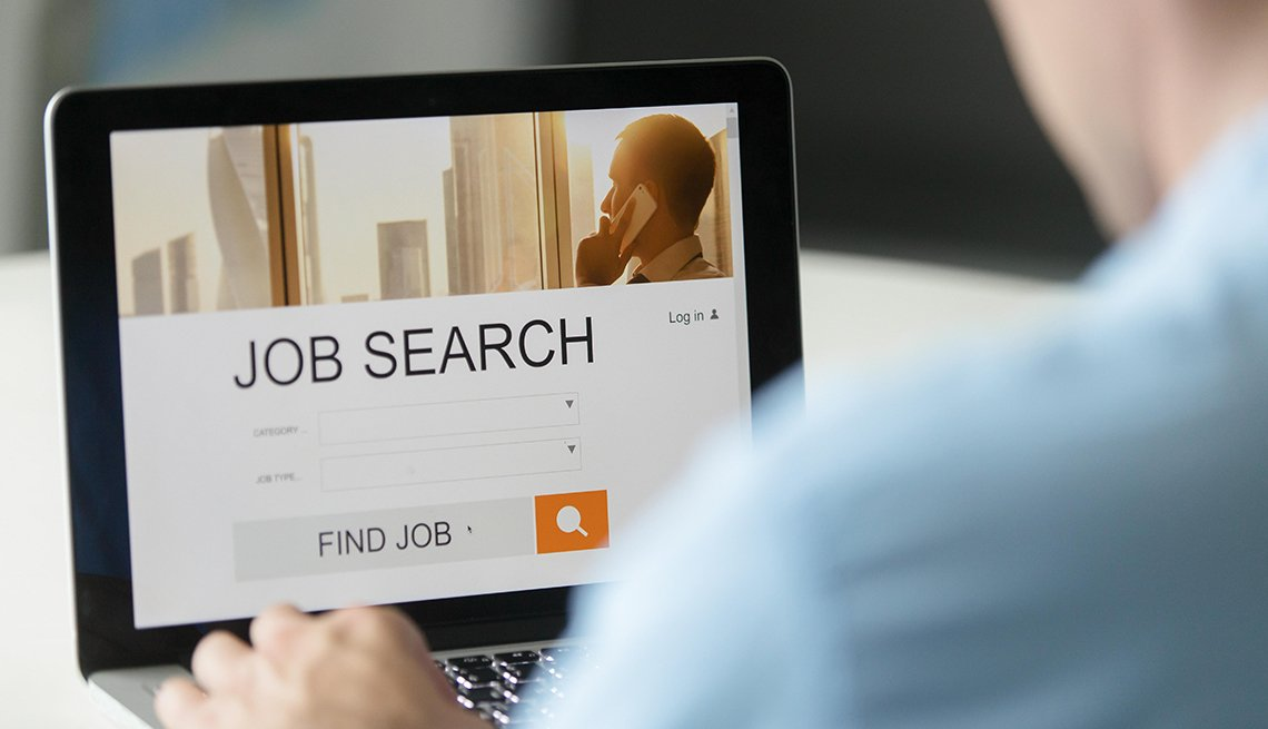 Hombre buscando trabajo en una computadora.