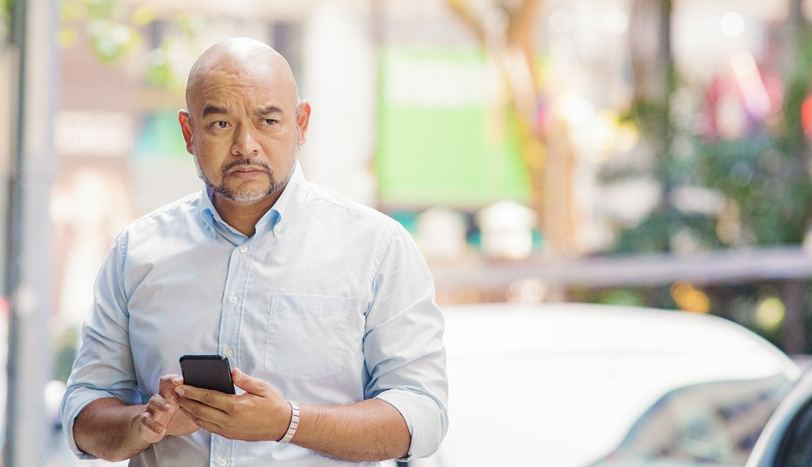 Man with smartphone in hand looking confused, lost