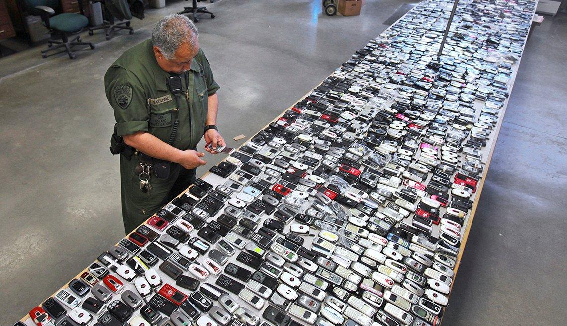 Guardia de una prisión frente a una mesa llena de teléfonos móviles ilegales.